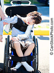 Father helping disabled child in wheelchair - Young disabled...