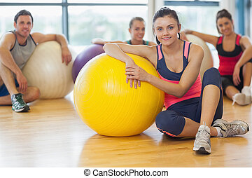 Instructor and fitness class with exercise balls at gym -...