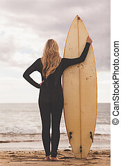 Rear view of a blond in wet suit with surfboard at beach -...