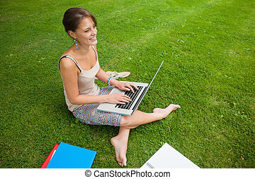 Student using laptop with books at