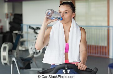 Tired woman drinking water while working out at spinning...