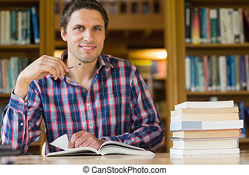 Smiling mature student studying at desk in the library -...