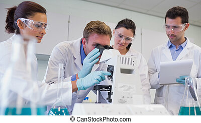Scientists with microscope in the l - Scientist using...