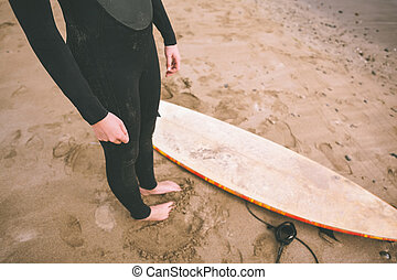 Low section of woman in wet suit with surfboard at beach -...