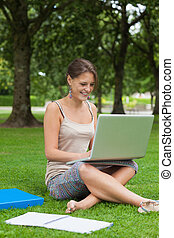 Smiling student using laptop with books at the park