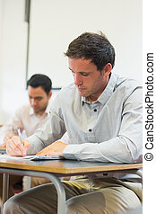 Mature students taking notes in classroom - Mature students...