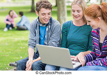 Young college students using laptop in park - Group of young...