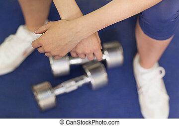 Low section of a tired woman with dumbbells in gym - Low...
