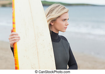 Beautiful young woman with surfboard on beach - Side view of...