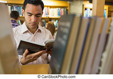 Mature student reading book by shelf in library - Close-up...