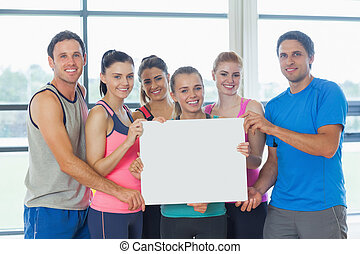 Portrait of a group of fitness class holding blank paper at...