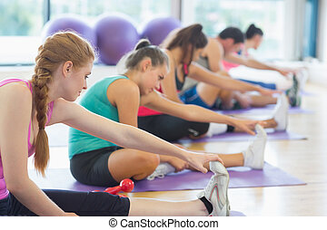 Fitness class and instructor stretching legs in bright...