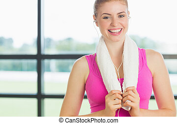 Portrait of a smiling young woman with towel around neck listening to music in fitness studio