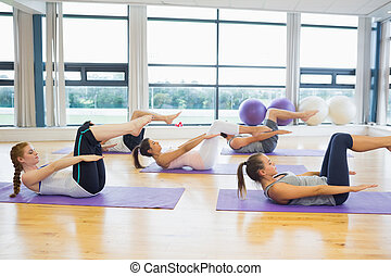 Class stretching on mats at yoga class in fitness studio -...