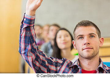 Close-up of a male student raising hand by others in...