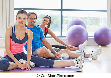 Fitness class and instructor sitting on exercise mats -...