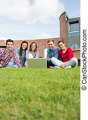 Students with laptop in the lawn ag - Group portrait of...