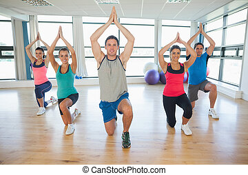 Fitness class and instructor kneeling in Namaste position at...
