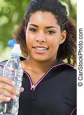 Close up portrait of a tired woman with water bottle in park