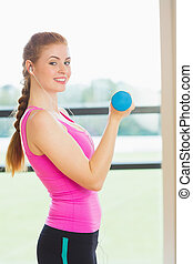 Side view portrait of a fit young woman exercising with...