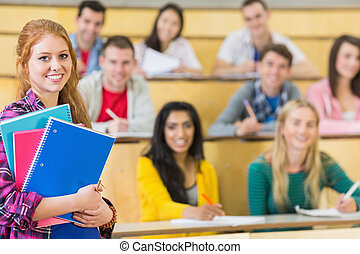Smiling female with students sitting at the lecture hall -...