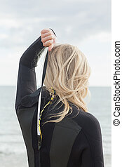 Rear view of a blond in wet suit standing at beach - Rear...