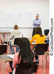 Attentive students with teacher in the classroom - Rear view...