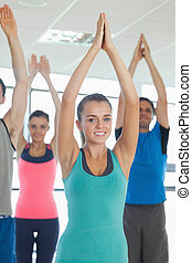 Fitness class with hands joined at exercise studio -...
