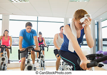 Tired people working out at spinning class - Determined and...