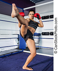 Female boxer performing an air kick in the ring