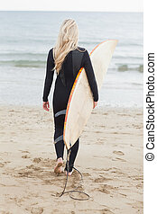 Rear view of a woman in wet suit holding surfboard at beach...