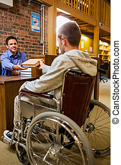 Student in wheelchair at the library counter - Male student...