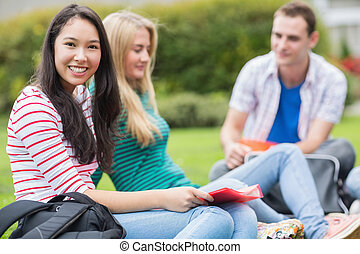 Young college students sitting in the park