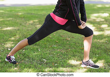 Low section of woman doing stretching exercise in park - Low...
