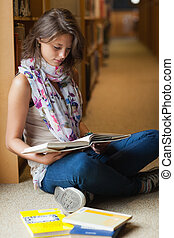 Female student reading a book in the library aisle - Full...