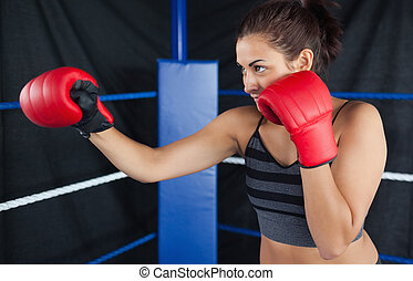 Determined female boxer practicing - Determined young female...