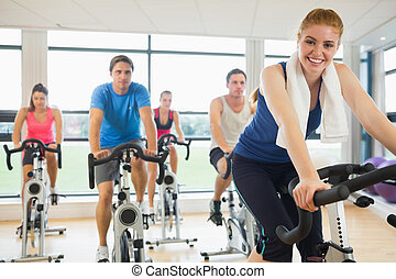 Happy woman teaches spinning class - Portrait of a happy...
