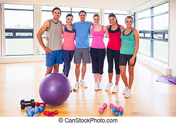 Full length portrait of fitness class at exercise room -...
