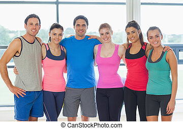 Portrait of a group of fitness class at exercise room -...