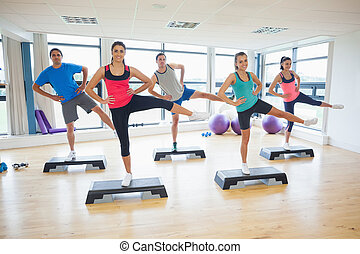 Instructor with fitness class performing step aerobics...