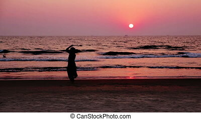 Woman dancing at sunset - Silhouette of woman dancing at...