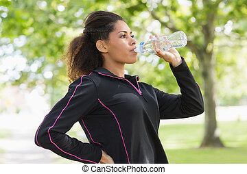 Tired healthy woman drinking water