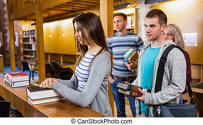 Students in a row at the library counter - Young students in...