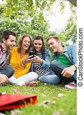 Happy college students looking at mobile phone in park -...