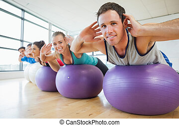 Portrait of class exercising on fitness balls in a row