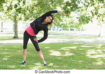 Full length portrait of a healthy young woman doing stretching exercise in the park