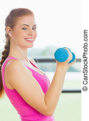 Fit young woman exercising with dumbell