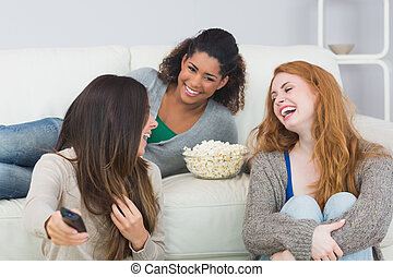 Cheerful friends with remote contro - Cheerful young female...