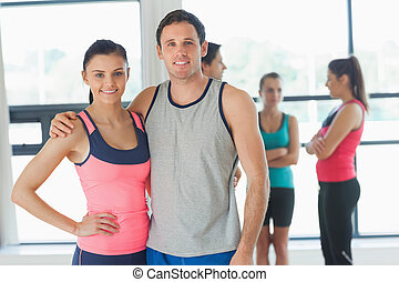 Fit couple with friends standing in background in exercise...