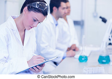 Researchers working on experiments in the laboratory - Side...